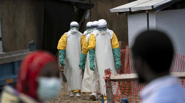 Health workers wearing protective gear begin their shift at an Ebola treatment centre (JErome Delay/AP)