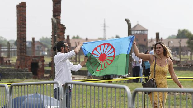 People display a Romani flag to commemorate the Roma and Sinti people killed by Nazi Germany in the Second World War, during ceremonies at Oswiecim, formerly known as Auschwitz (Czarek Sokolowski/AP)