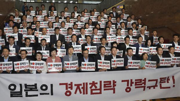 Members of the ruling Democratic Party shout slogans during a rally to denounce Japan's new trade restrictions on South Korea at the National Assembly in Seoul, South Korea (HA Sa-hun/AP)