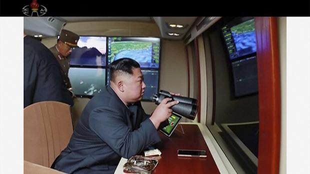 North Korean leader Kim Jong Un, equipped with binoculars, supervises a rocket launch test (AP)