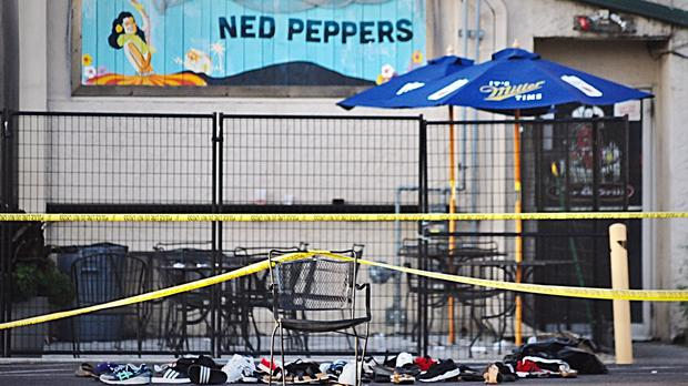 Police tape drapes over a chair near a pile of shoes after a mass shooting in Dayton, Ohio (Marshall Gorby/Dayton Daily News/AP)
