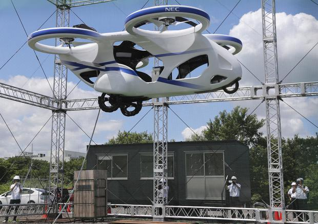 Futuristic flying auto  hovers above the ground for about a minute