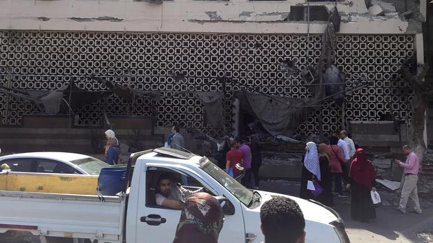 People survey the aftermath of a car crash outside the National Cancer Institute in Cairo, Egypt (Maya Alleruzzo/AP)