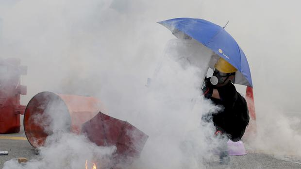 A protester is shrouded by tear gas in Hong Kong (Kin Cheung/AP)