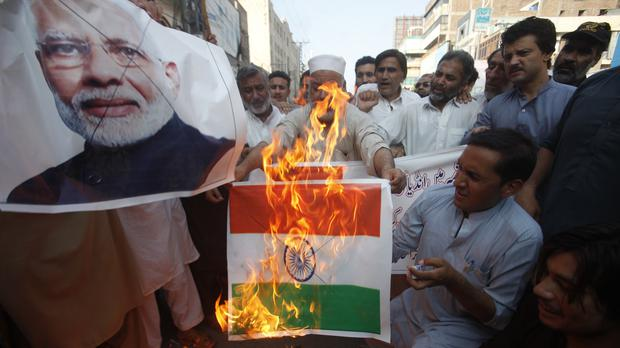Pakistanis burn a representation of an Indian flag and a poster of Indian PM Narendra Modi (AP)