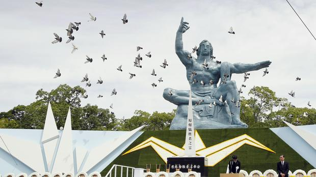 Doves fly over the Statue of Peace during a ceremony at Nagasaki Peace Park (Kyodo/AP)
