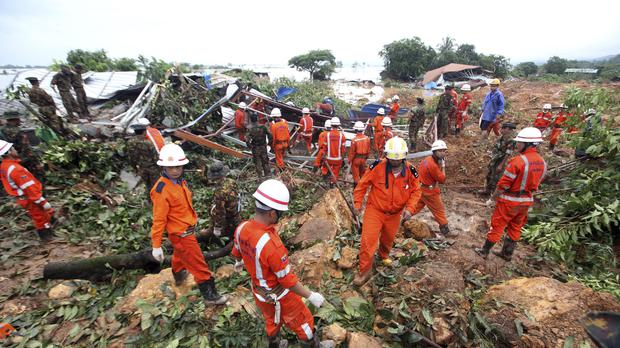 Members of a rescue team gather at a landslide-hit area in Paung township, Mon state (AP)