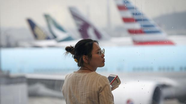 A woman reacts as airplanes are parked at the Hong Kong International Airport (Vincent Thian/AP)
