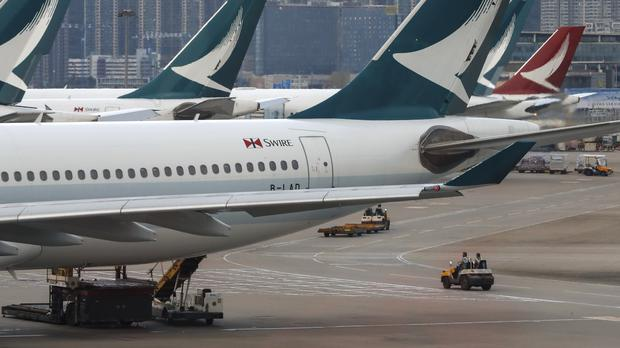 Ground crew drive past Cathay Pacific Airways planes (Vincent Thian/AP)
