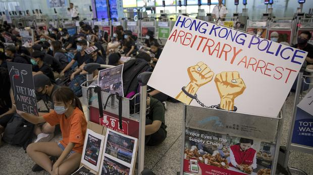 Protesters stage a sit-in rally at the departure gates of the Hong Kong International Airport (Vincent Thian/AP)