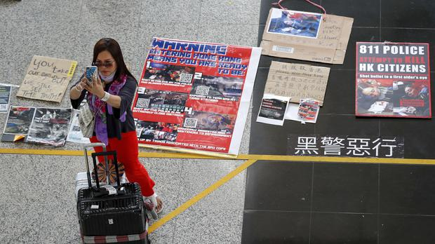 A traveller takes a smartphone photo near placards and posters placed by protesters at the airport in Hong Kong (Vincent Thian/AP)