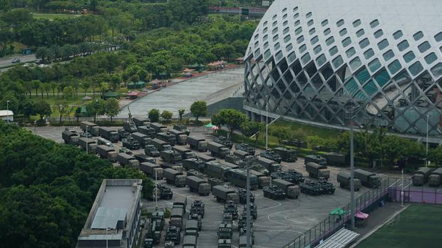Armoured vehicles and troop lorries are parked by Shenzhen Bay Stadium in Shenzhen, China (Dake King/AP)
