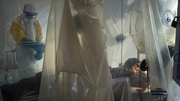 Health workers wearing protective gear check on a patient isolated in a plastic cube at an Ebola treatment centre in Beni (Jerome Delay/AP)
