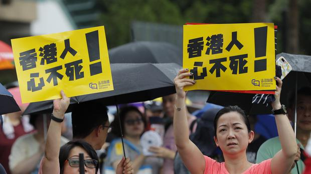 Participants hold up signs that read 'Hong Kongers won't give up!' during a rally in Hong Kong (Vincent Thian/AP)