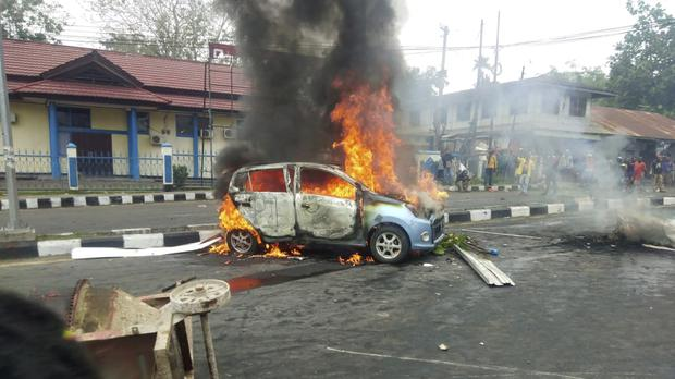 A car burns during a protest in Indonesia (Safwan Ashari Raharusun/AP)