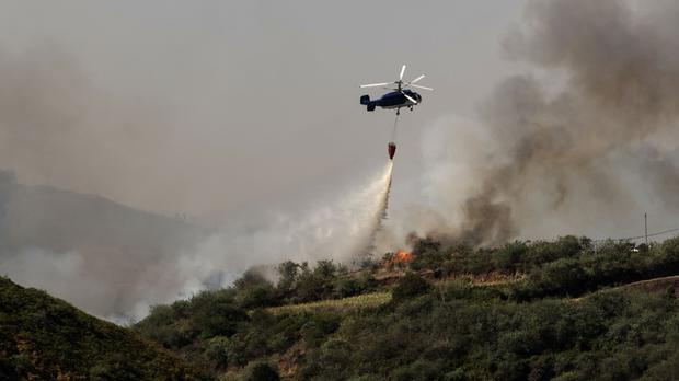A helicopter operates over a wildfire in the Canary Islands (AP)