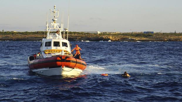 A man who threw himself in the water from the Open Arms vessel, is intercepted by coastguards (AP Photo/Francisco Gentico)