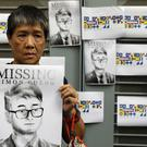 A supporter holds a poster of Simon Cheng Man-kit outside of the British Consulate in Hong Kong (Vincent Yu/AP)
