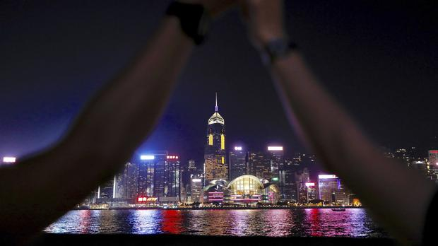 Demonstrators link hands as they gather at the Tsim Sha Tsui waterfront (Vincent Yu/AP)