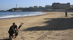 French military perform a de-mining sweep along the beach inside the red zone in Biarritz *Peter Dejong/AP)