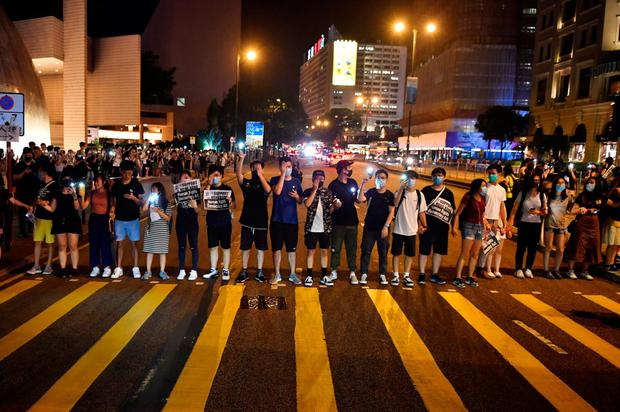 Symbolic: Protesters form a human chain on the street outside the Cultural Centre in Hong Kong yesterday. Photo: Lillian SUWANRUMPHA/AFP/Getty Images