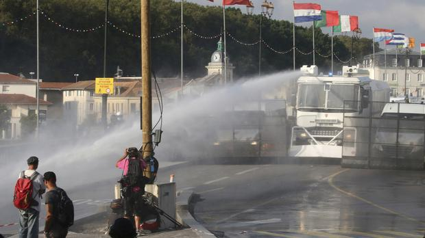 Police fire water cannon at protesters (Bob Edme/AP)