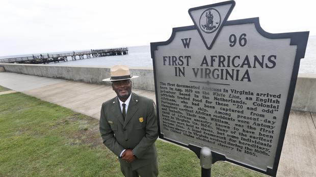 Terry E. Brown, superintendent of the Fort Monroe National Monument, next to a marker that signifies the spot of the first landing of Africans in America 400 years ago (Steve Helber/AP)