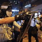A policeman points a weapon during a protest in Hong Kong on Sunday (Vincent Yu/AP)