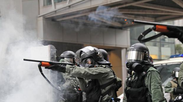A riot policeman fires his weapon during a confrontation with demonstrators during a protest in Hong Kong (Kin Cheung/AP)