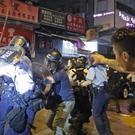 A man throws a brick to policemen during a protest in Hong Kong (Kin Cheung/AP)