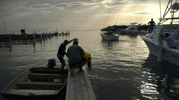 People arrive to a private harbor to move boats away for protection ahead of the arrival of Tropical Storm Dorian (Ramon Espinosa/AP)