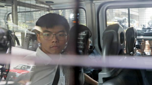 Pro-democracy activists Joshua Wong, left, and Agnes Chow, are escorted in a police van (Kin Cheung/AP)