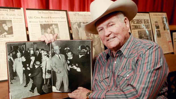 Jim Leavelle holding the 1963 photograph, as he escorted Lee Harvey Oswald moments before he is shot in Dallas (Sandra J. Milburn/AP)