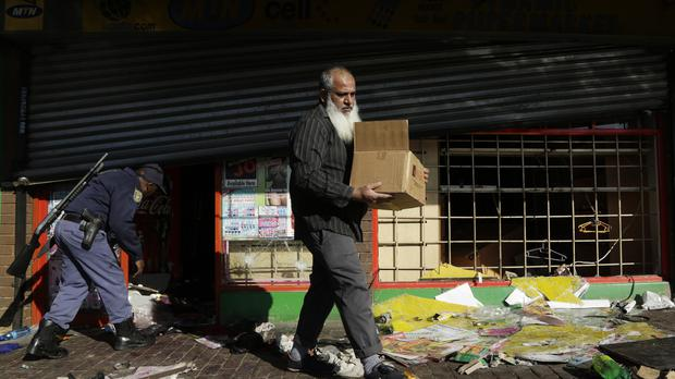 A business owner carries goods out of his damaged shop caused by looters in Germiston, east of Johannesburg (AP)