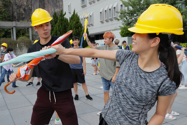 Brolly good: Hong Kong students use umbrellas to practice self-defence techniques to prevent possible violence during protests. Photo: AP