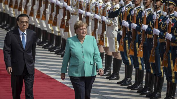 Chinese Premier Li Keqiang, left, and German Chancellor Angela Merkel inspect an honour guard during a welcome ceremony in Beijing (Roman Pilipey/Pool Photo via AP)