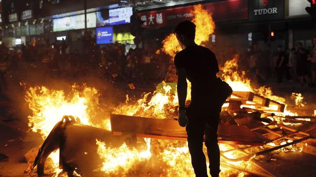 Protesters stand near burning items during a protest in Hong Kong (Kin Cheung/AP)