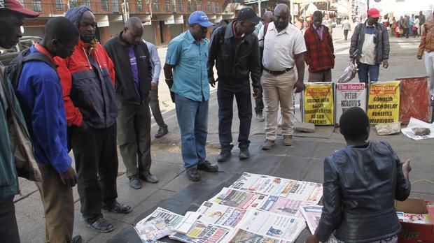 People gather around a newspaper vendor to read headlines on a street in Harare (Tsvangirayi Mukwazhi/AP)