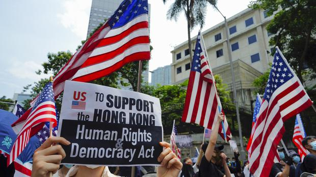 Protesters wave US flags and carry placards during a protest in Hong Kong (Vincent Yu/AP)
