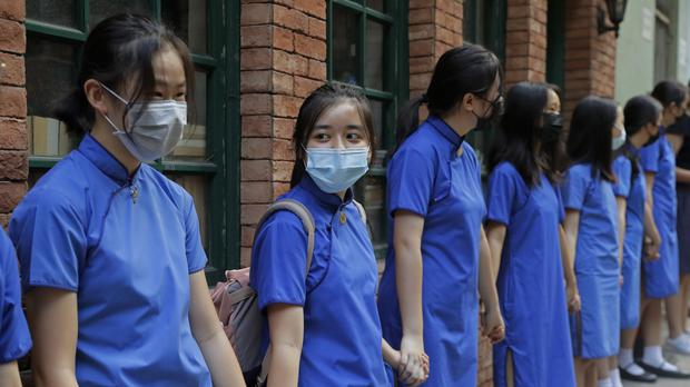Students wearing mask hold hands to surround St Stephen's Girls' College in Hong Kong (AP)