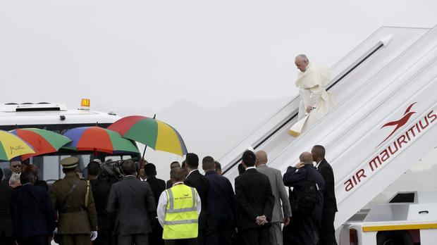 Pope Francis steps off the plane as he arrives in Port Louis, Mauritius (Alessandra Tarantino/AP)