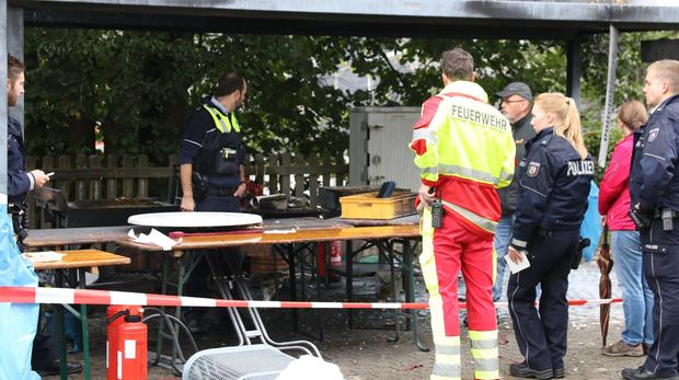 Police officers investigate a booth after an explosion at a village festival in Freudenberg, Germany (Berthold Stamm/AP)