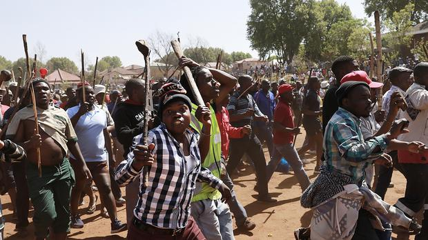 Residents of local hostels march with homemade weapons in Johannesburg (AP)
