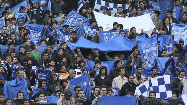 Supporters of Iranian soccer team Esteghlal, hold flags of their favourite team (Vahid Salemi/AP)