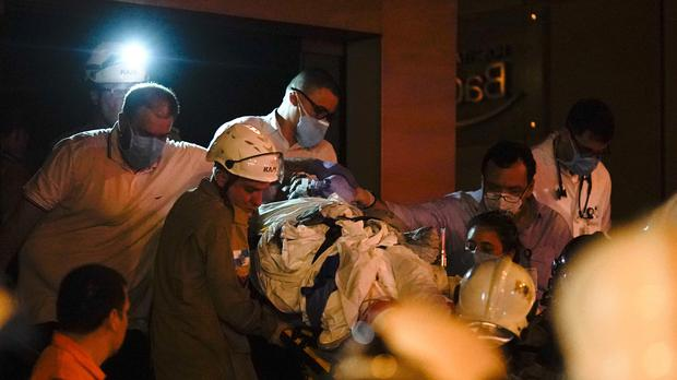 A patient is evacuated from a burning hospital in Rio de Janeiro, Brazil (Leo Correa/AP)