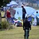 French police officers watch migrants packing their belongings in a camp at Grande Synthe, northern France (AP)