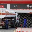Workers refuel the tank at a petrol station in Saudi Arabia (Amr Nabil/AP)