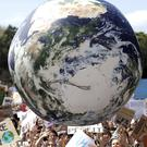 A large inflatable globe is bounced through the crowd as thousands of protesters join a climate change rally in Sydney (Rick Rycroft/AP)