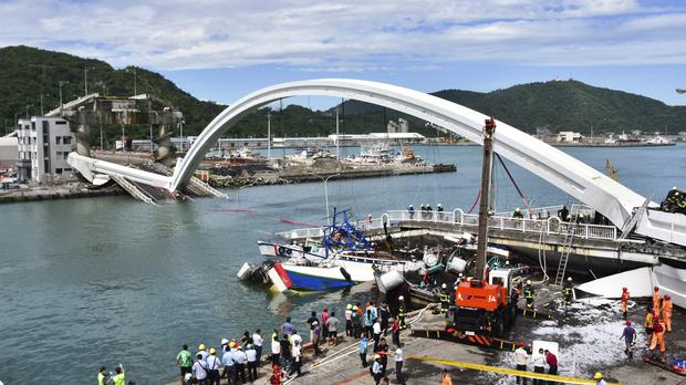 Rescuers work near the site of a collapsed bridge in Nanfangao, eastern Taiwan. Tuesday, Oct. 1, 2019. A towering bridge over a bay in eastern Taiwan has collapsed sending an oil tanker truck falling onto boats in the water below. A disaster relief official said the collapse set off a fire and at least 10 people have been hurt. (AP Photo)
