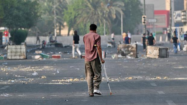 An Injured protester walks towards Tahrir Square to join anti-government protesters in central Baghdad (Hadi Mizban/AP)